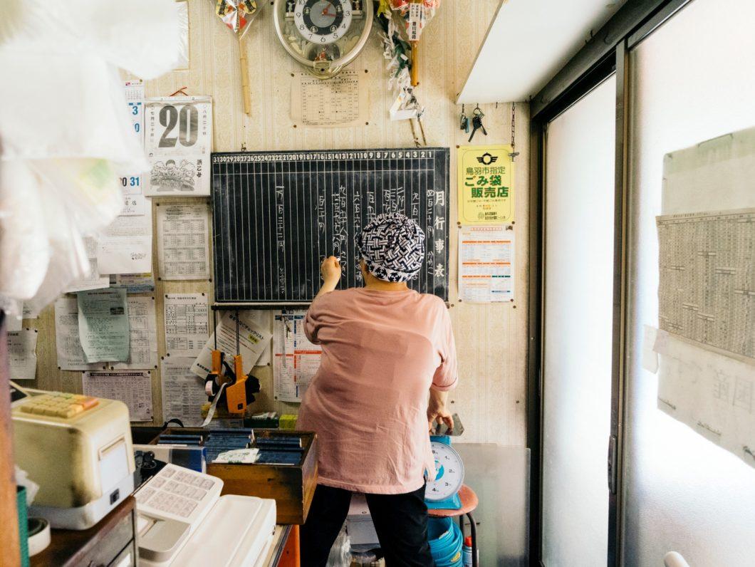 菅島杉田商店でツケを記録する店員