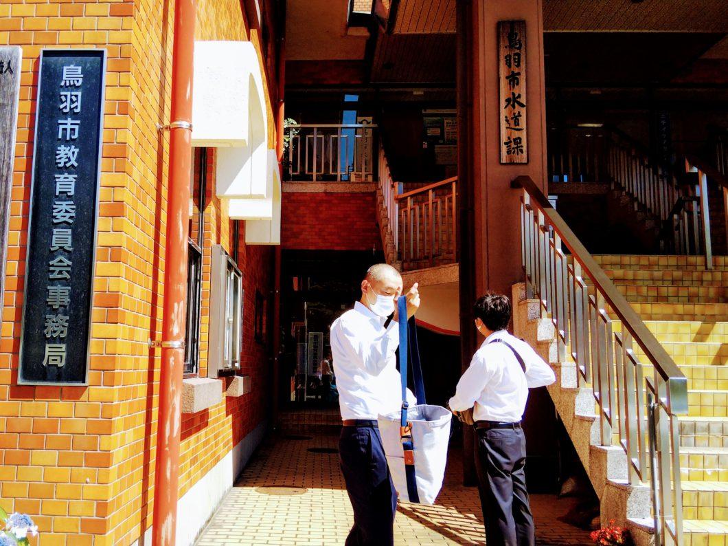 鳥羽市教育委員会の入口に立つ会員