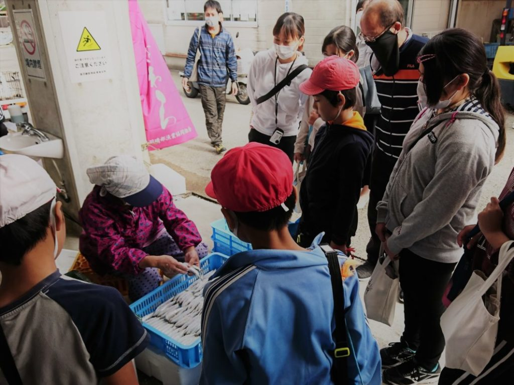 漁協の市場を見学する児童たち