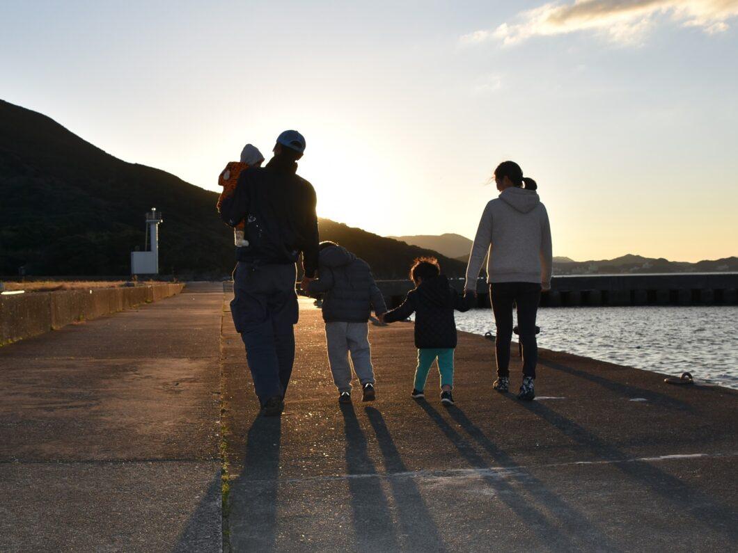 夕日に向かってあるく5人家族の後ろ姿