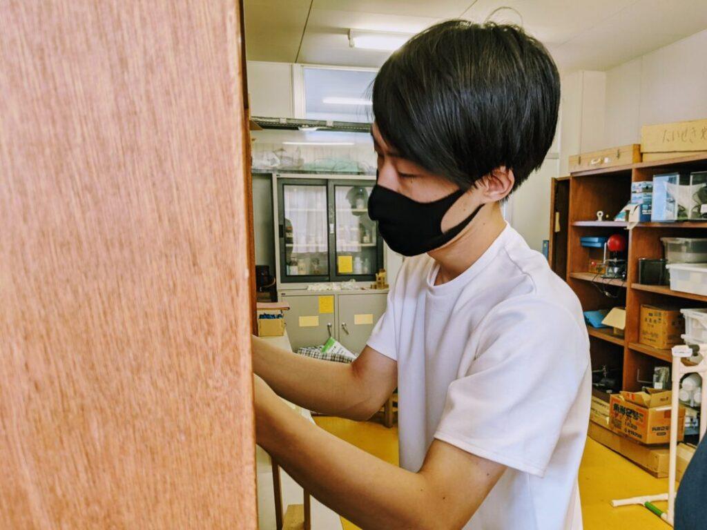 菅島小学校の理科準備室で器具を確認する横尾氏